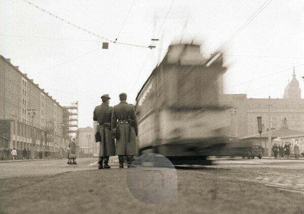 Two People's Police officers watch the morning traffic on Prager Strasse in Dresden