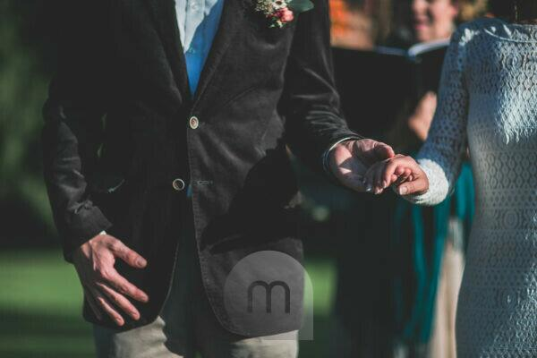 Alternate bridal couple at spiritual wedding ceremony outdoors, detail, hands hold