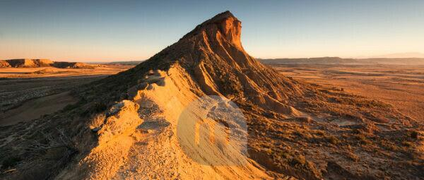 Panoramic view of mountains in the Bardena Reales desert at sunset with blinding light, Navarra, Spain