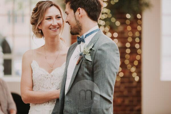 Bridal couple, standing, eye contact, smiling, half portrait, detail,
