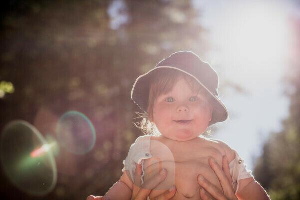 held up toddler, smiling, looking into camera, backlight,