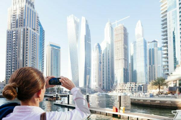 Dubai skyscrapers with Dubai Marina, female tourist taking a picture