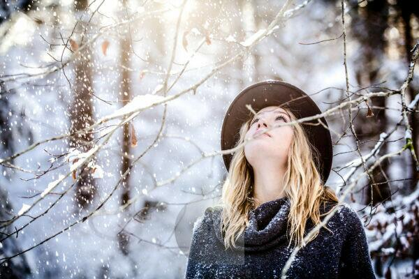 Young woman with blond hair dressed wintry, looking upwards