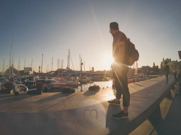 young tourist man staring to the sunset at Barcelona port