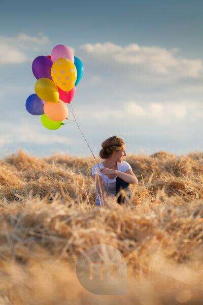 Young woman with colorful air balloons in the mown corn field