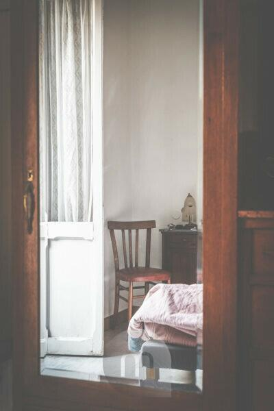 A chair, a door and a bed, a furniture of 50'er / 60'er years seen in the mirror