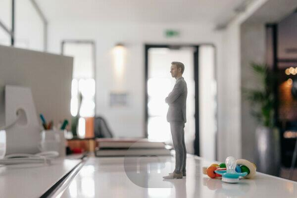Businessman figurine standing on desk with pacifier and toys