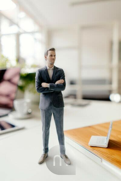 Businessman figurine standing on a desk with mobile devices