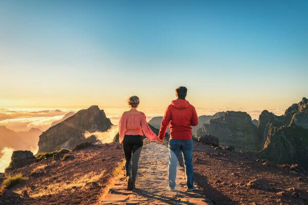 A couple walks hand in hand on Madeira over the mountain Pico do Arieiro. You can see the cloud cover at sunset.