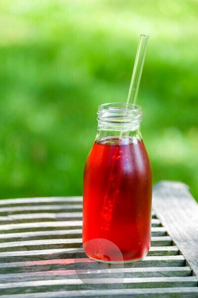 Small bottle with red lemonade on a wooden table in the garden