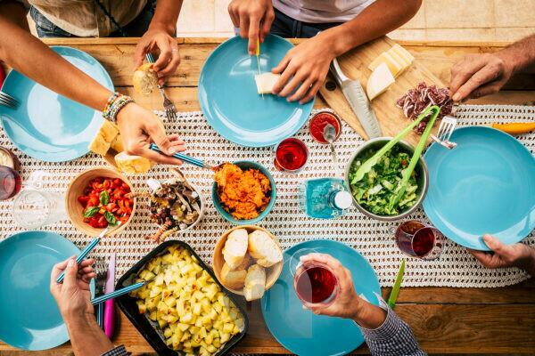 People eating together in friendship or family celebration with table full of food viewed from vertical top - friends and have fun concept - colors and background with wooden table