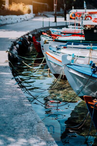 Colorful fishing Boats docked alongside close to quay on the coast of greek island, mediterranean sea scene.