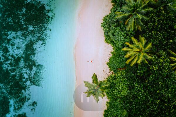 Aerial view of a young woman relaxing on the tropical paradise sandy beach surrounded by palm trees and crystal clear azure ocean shallow water.