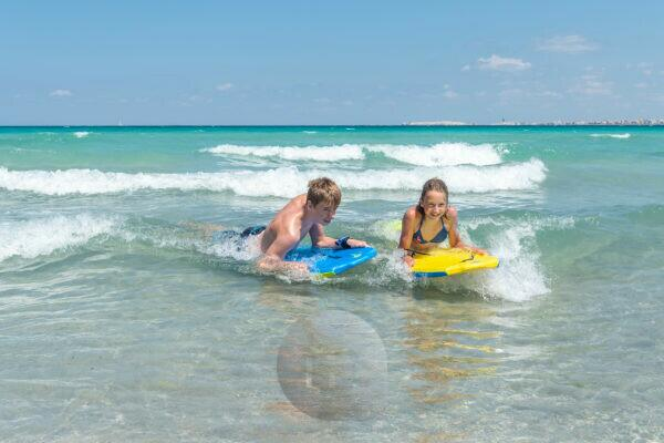 Lido Pizzo, Gallipoli, Salento, Apulia, Italy, Europe. Two kids have fun with their bodyboards in the Ionian Sea