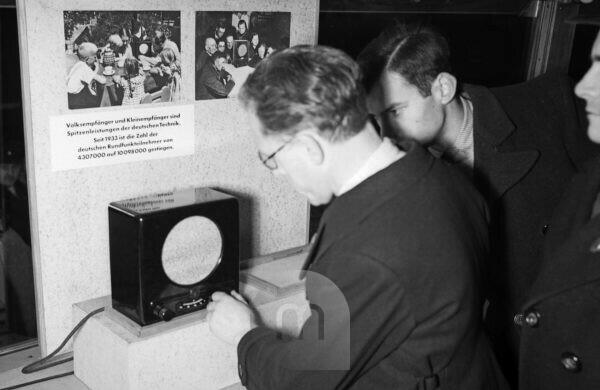 "Visitors walking through the exhibition of the ""Sonderfahrt der deutschen Technik"" propaganda exhibition, here the Volksempfänger radio, Germany 1930s."