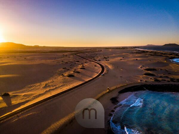 Beautiful aerial view of coast beach during the sunset -blue ocean and yellow sand and desert with sun light come from montains in background -travel and vacation concept