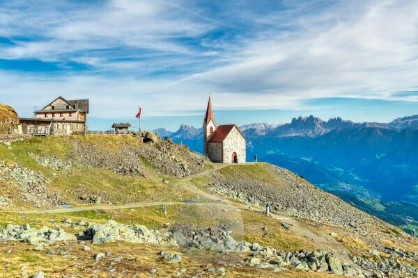 Latzfons, Klausen, Bolzano province, South Tyrol, Italy, Europe. The refuge and the pilgrimage church Latzfonser Kreuz with a view of the Dolomites with the Odle peaks