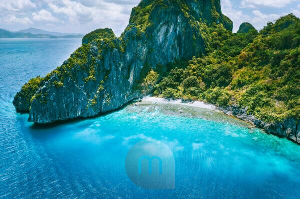 El Nido, Palawan. Aerial drone view of tropical Entalula Island. Huge steep rocks cliffs mountains with blue bay and beautiful intact coral reef. Island hopping tour trip.